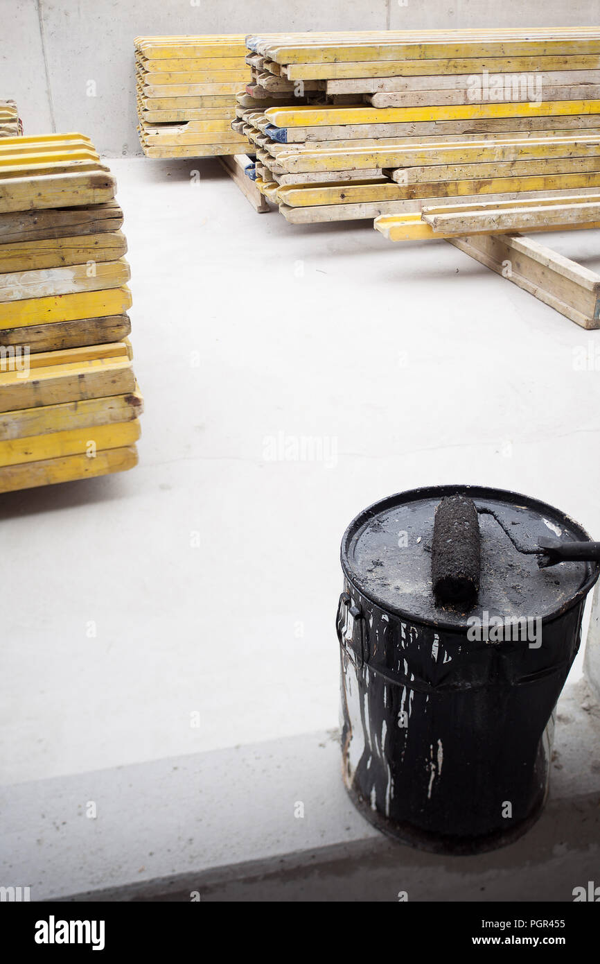 Barrel with painter roll on construction site with wood planks - Stock Image