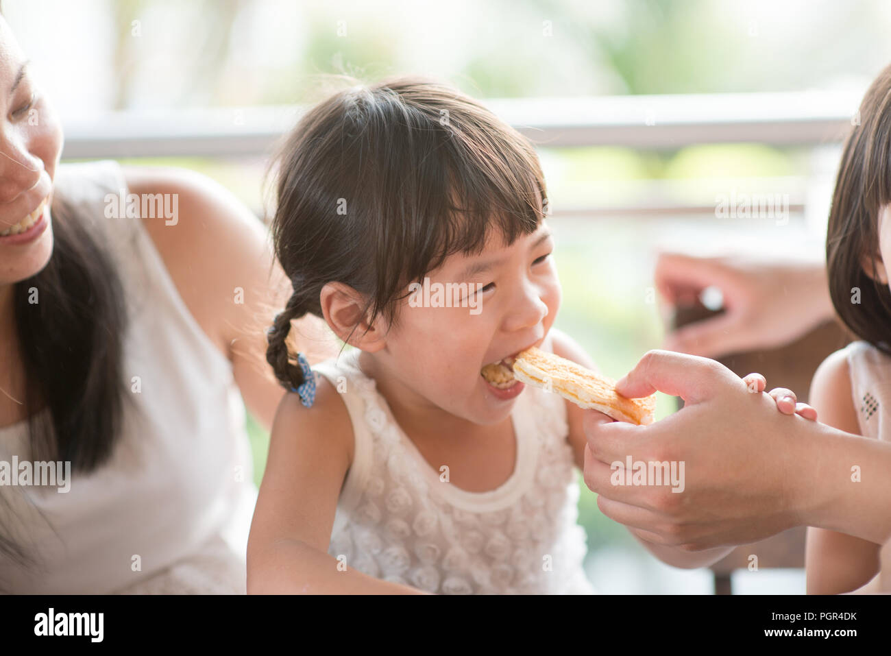 Daddy feed bread to child at cafe. Asian family outdoor lifestyle with natural light. - Stock Image