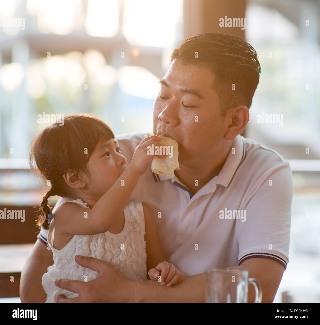 Child feeding bread to daddy at cafeteria. Asian family outdoor lifestyle with natural light. - Stock Image