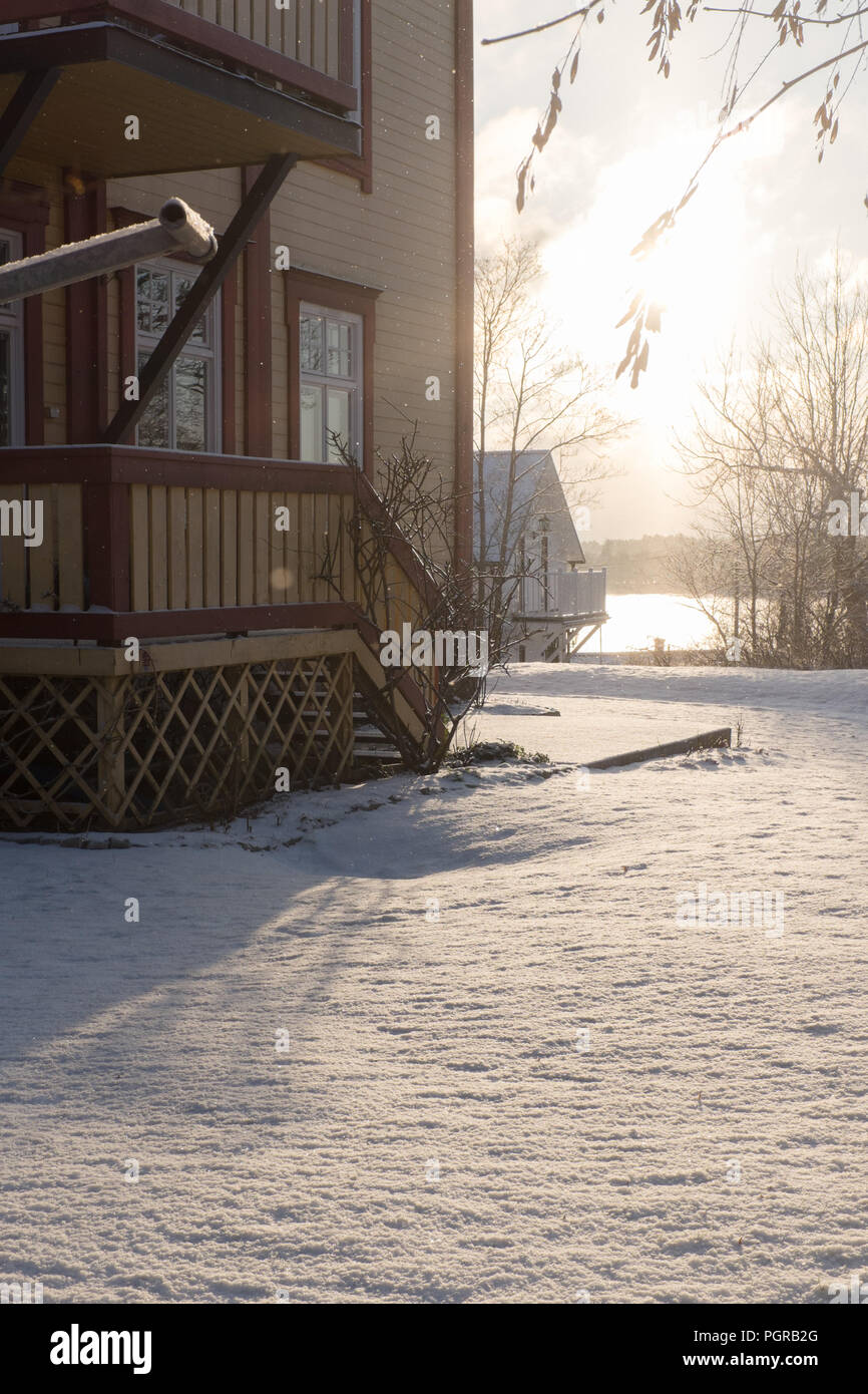 wooden swedish house in wintertime during sun dawn, located in the skerries near Stockholm - Stock Image