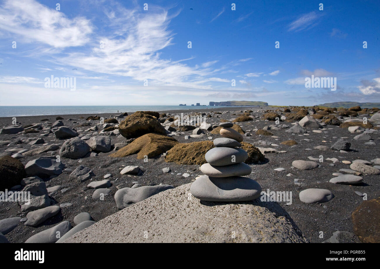 A black sand beach at Dyrholaey reserve near Vik Iceland. The cairn marks the area as elf habitat. - Stock Image