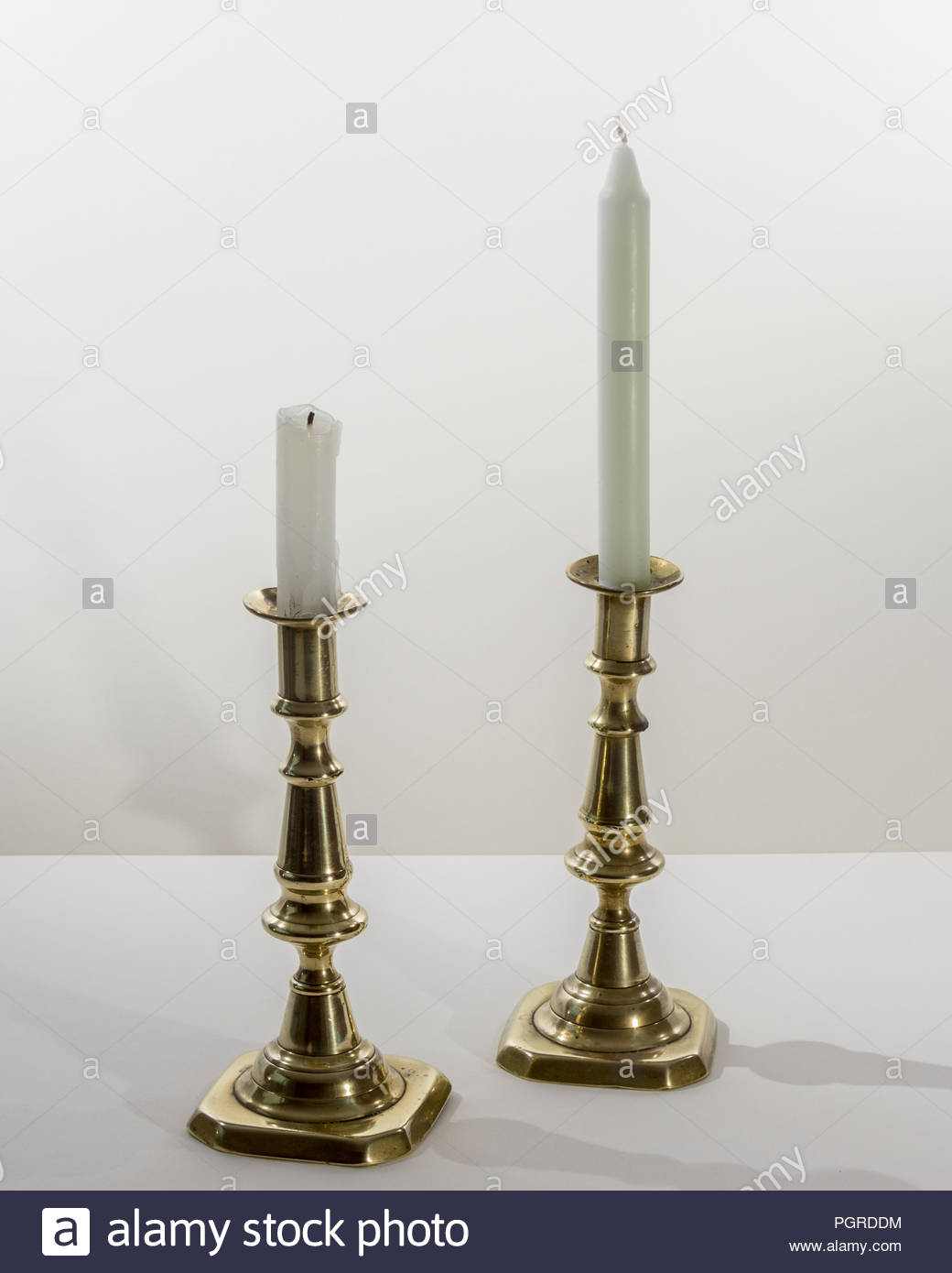 A pair of polished antique brass candlestick, with unlit candles on a white background Stock Photo