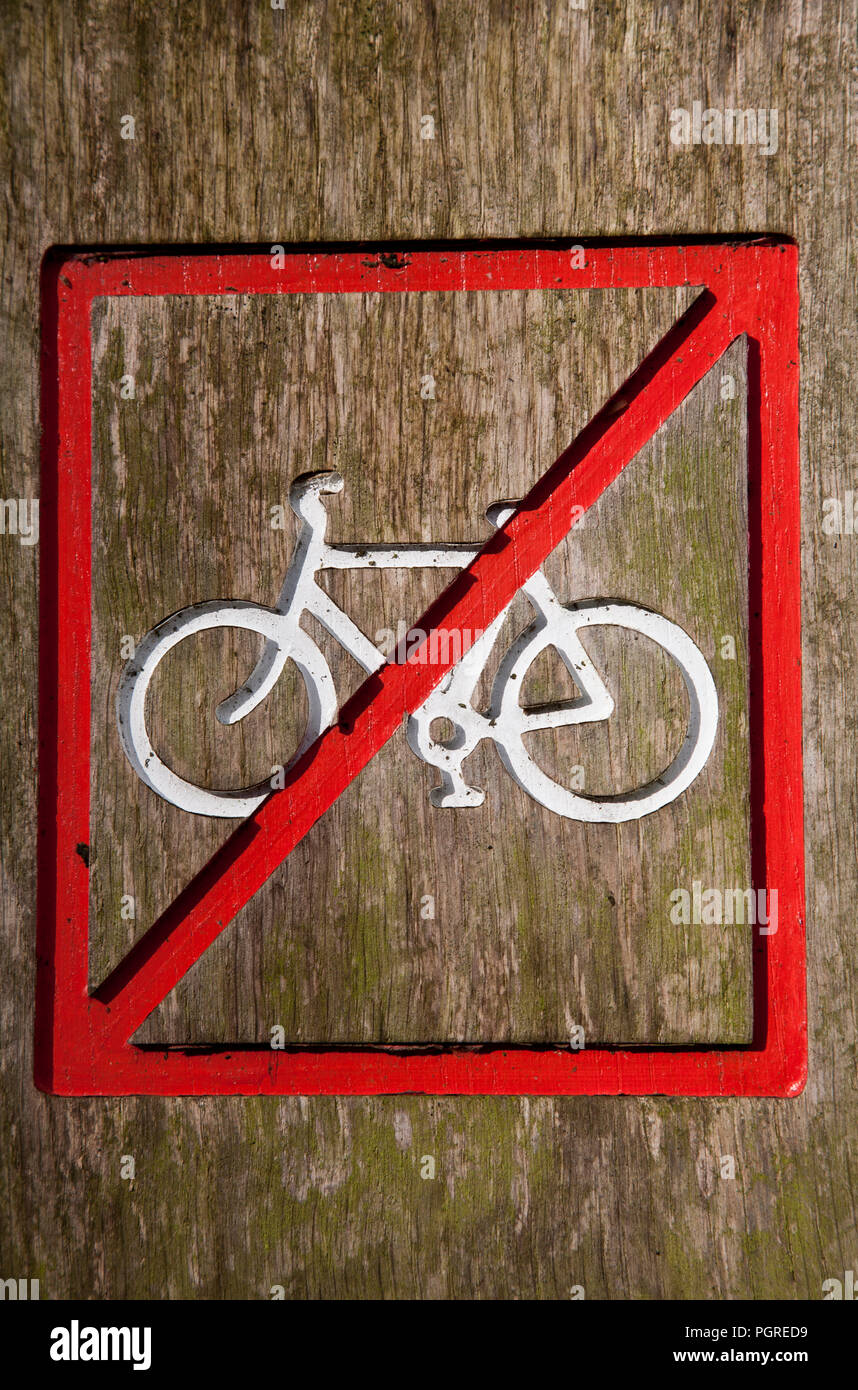 Close-up of a no cycling sign on a wooden post. - Stock Image