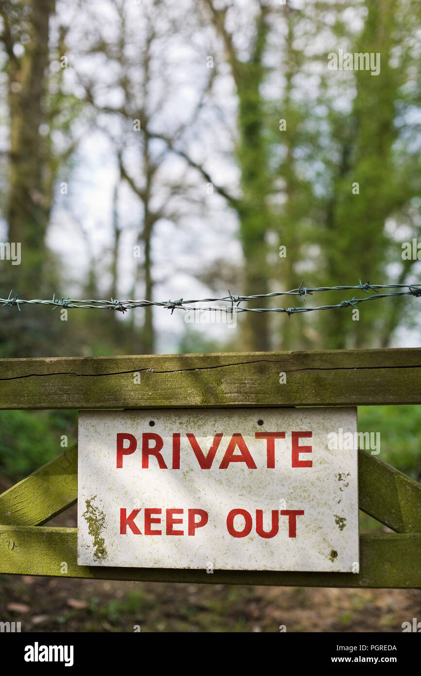 'Private Keep Out' sign on a gate in a woodland. - Stock Image