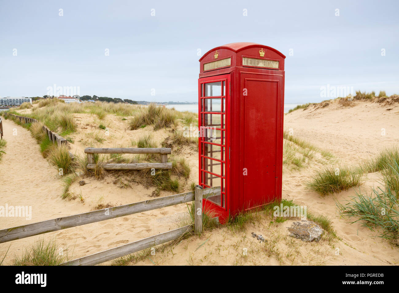 A bright red telephone box on the sand dunes at South Haven Point in Dorset at the end of the 630 mile South West Coast Path in England, UK. - Stock Image