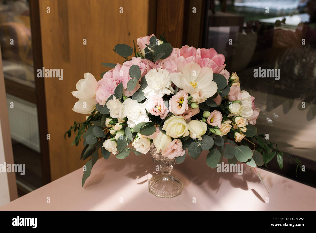 Composition from flowers - decoration of a table for guests. White candles in big glass vases - Stock Image