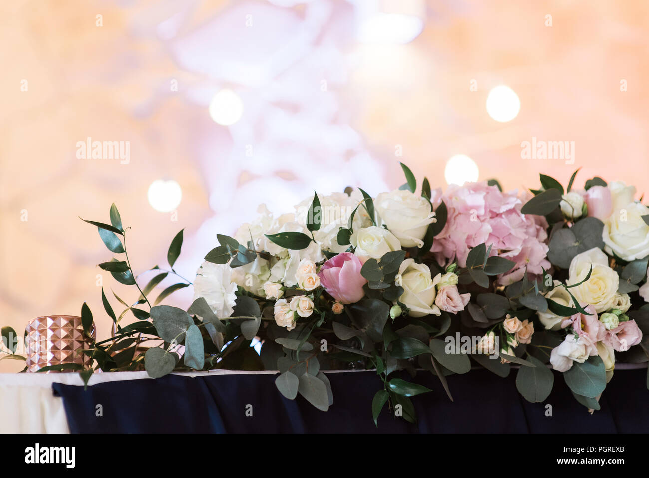 Beautiful Flowers In A Golden Vase On A White Table Stock Photo