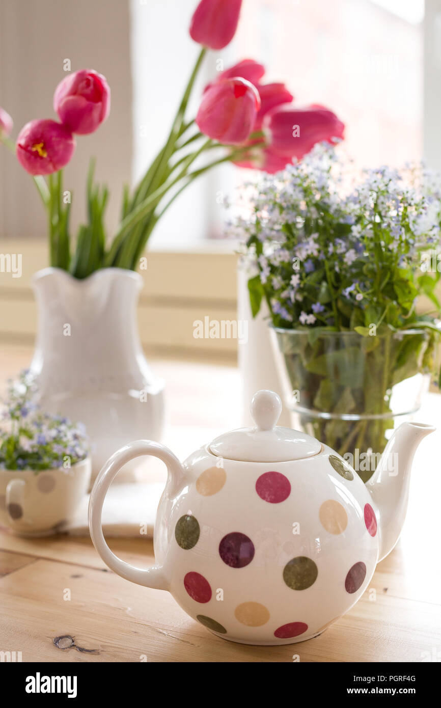 Teapot with dots and vases with beautiful spring flowers on the teapot with dots and vases with beautiful spring flowers on the wooden table decoration for home interior forget me not and tulips in vases flowers izmirmasajfo