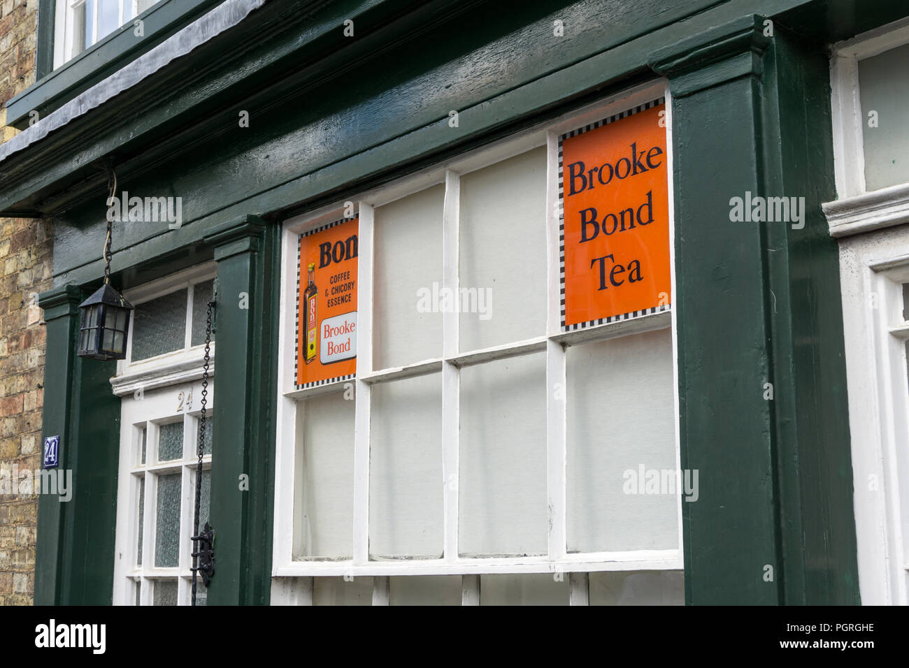 Frontage of an old shop, now converted to residential use, displaying vintage Brooke Bond Tea adverts; Kimbolton, UK - Stock Image