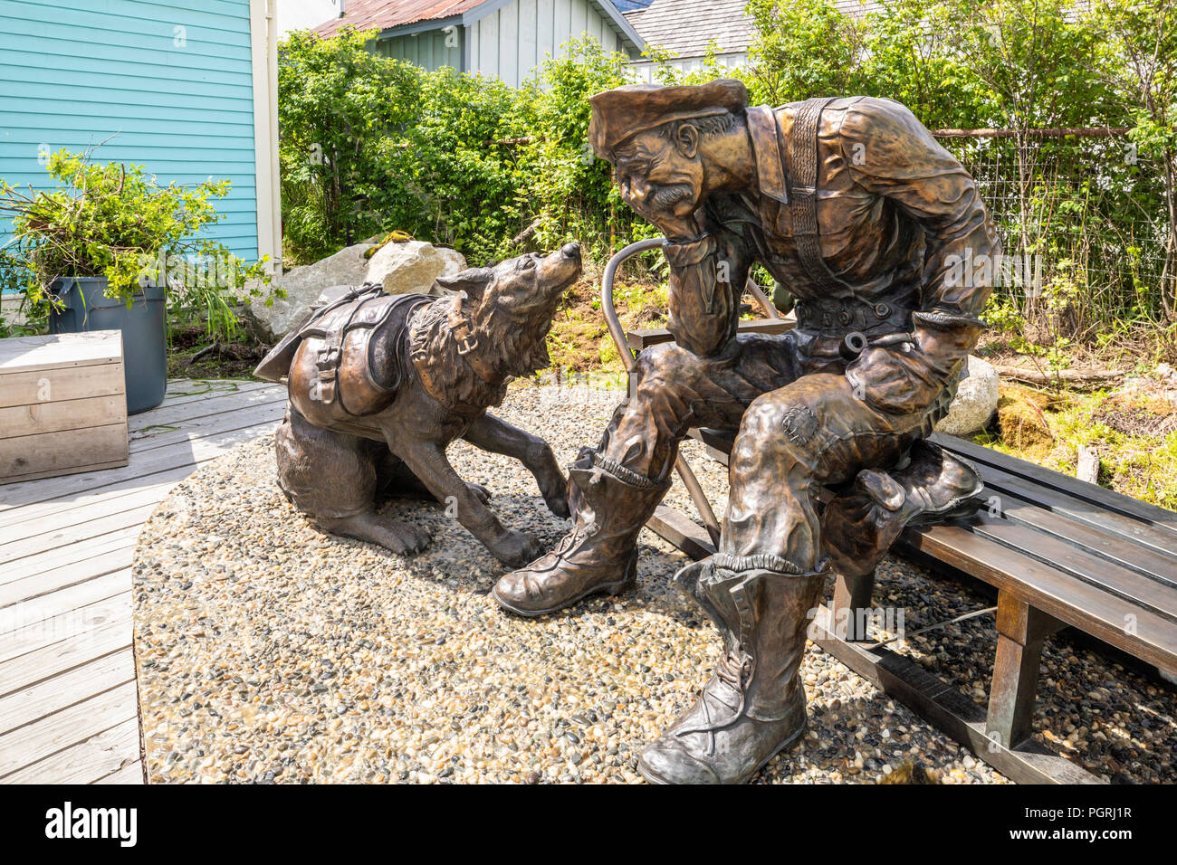 A sculpture of a prospector and his dog outside the Alaska Geographic Museum Store (National Park Service) in Skagway, Alaska, USA - Stock Image