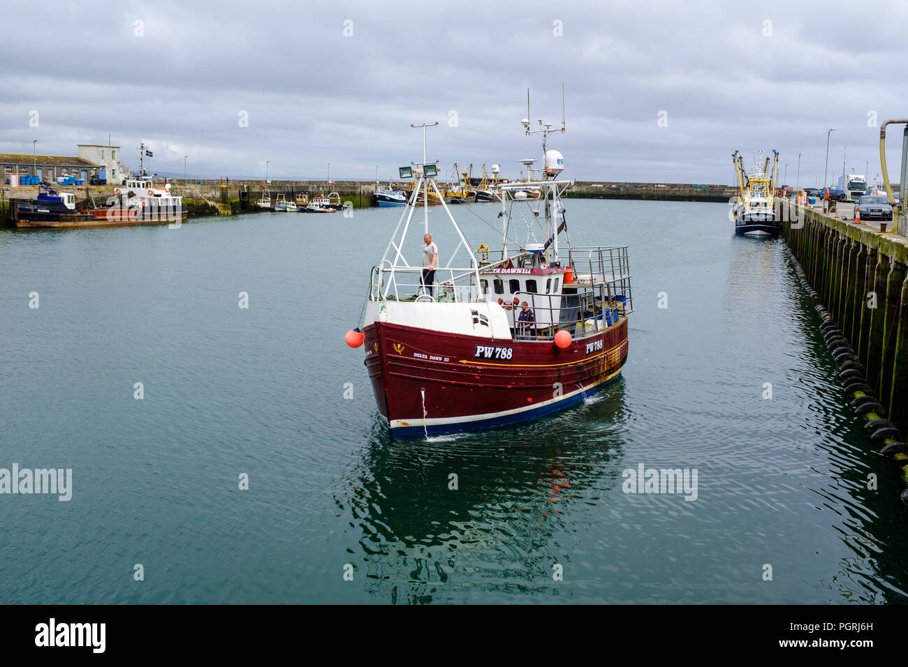 Fishing trawler boat returning to Newlyn harbour. In Newlyn, Cornwall, England. On 20th June 2018. - Stock Image