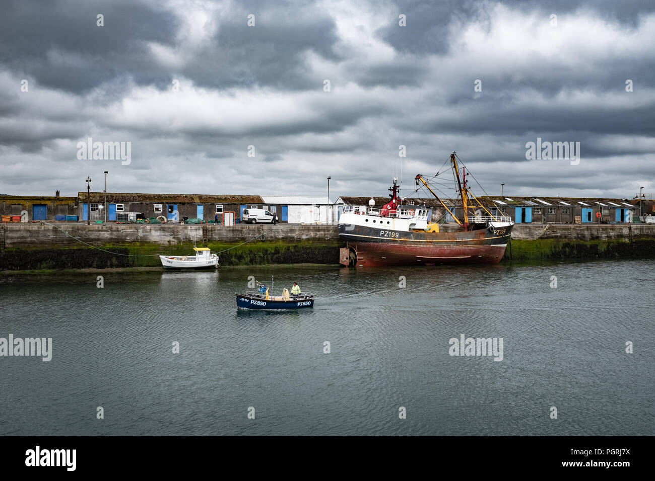 Small fishing boat returning to harbour, in Newlyn. In Newlyn, Cornwall, England. On 20th June 2018. - Stock Image