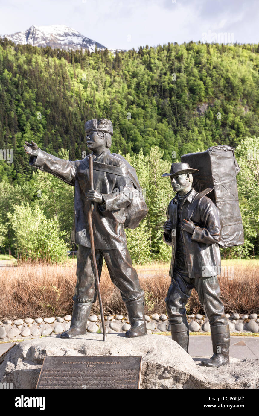 The Skagway Centennial Statue by Chuck Buchanan showing a typical prospector at the time of the Klondike Gold Rush being led by a native Tlingit guide - Stock Image