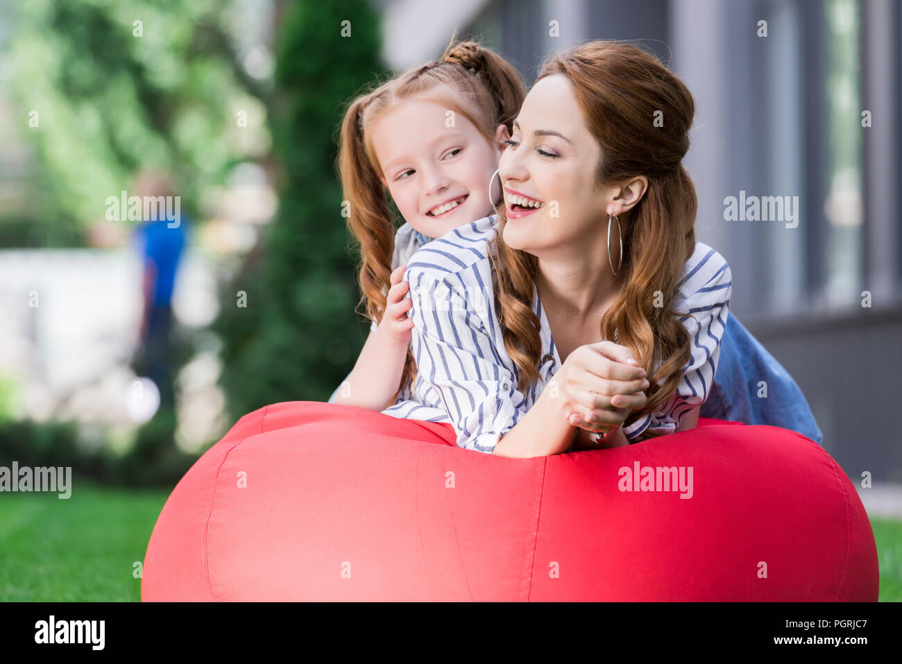 portrait of happy family resting on bean bag chair together - Stock Image