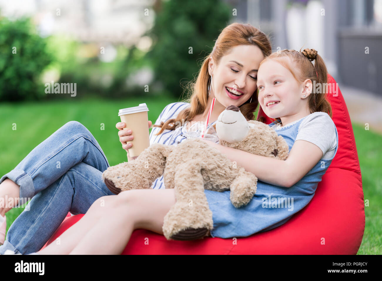 smiling mother with coffee to go and daughter with teddy bear resting on bean bag chair together - Stock Image