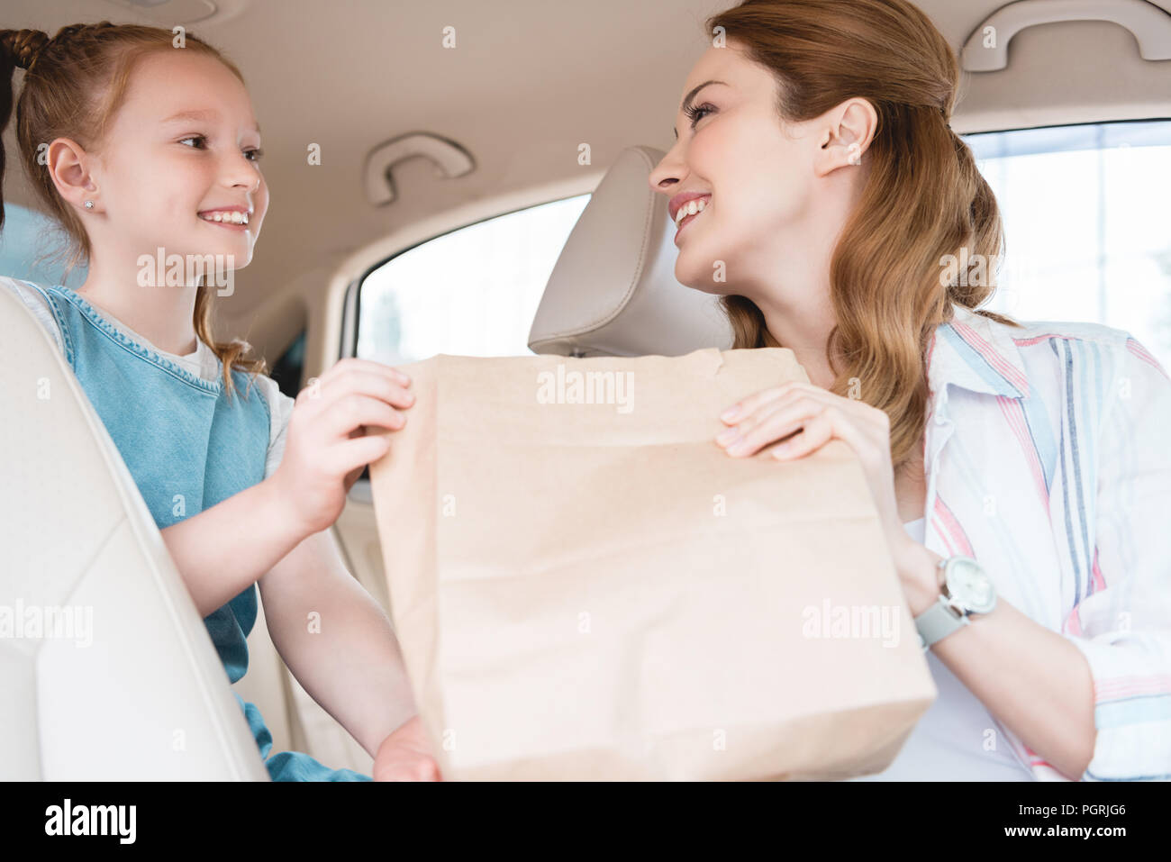 side view of smiling mother giving paper package with food to daughter in car - Stock Image