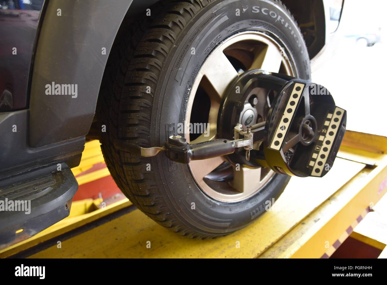 Tyre/tire fitting: a vehicle raised on a ramp and undergoing a wheel alignment test - Stock Image