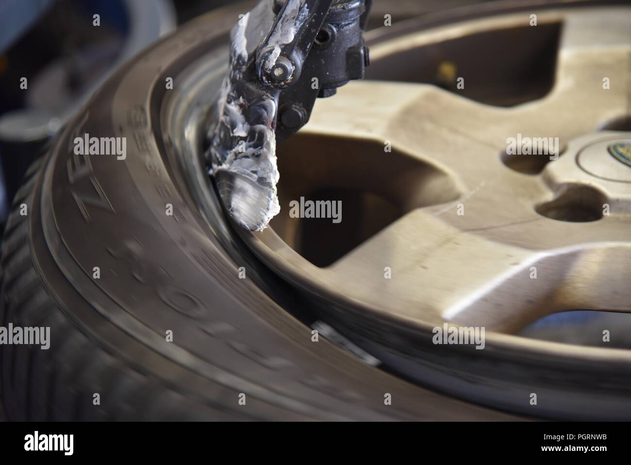 Tyre/tire fitting: a worn tyre being removed on a tyre changer - Stock Image