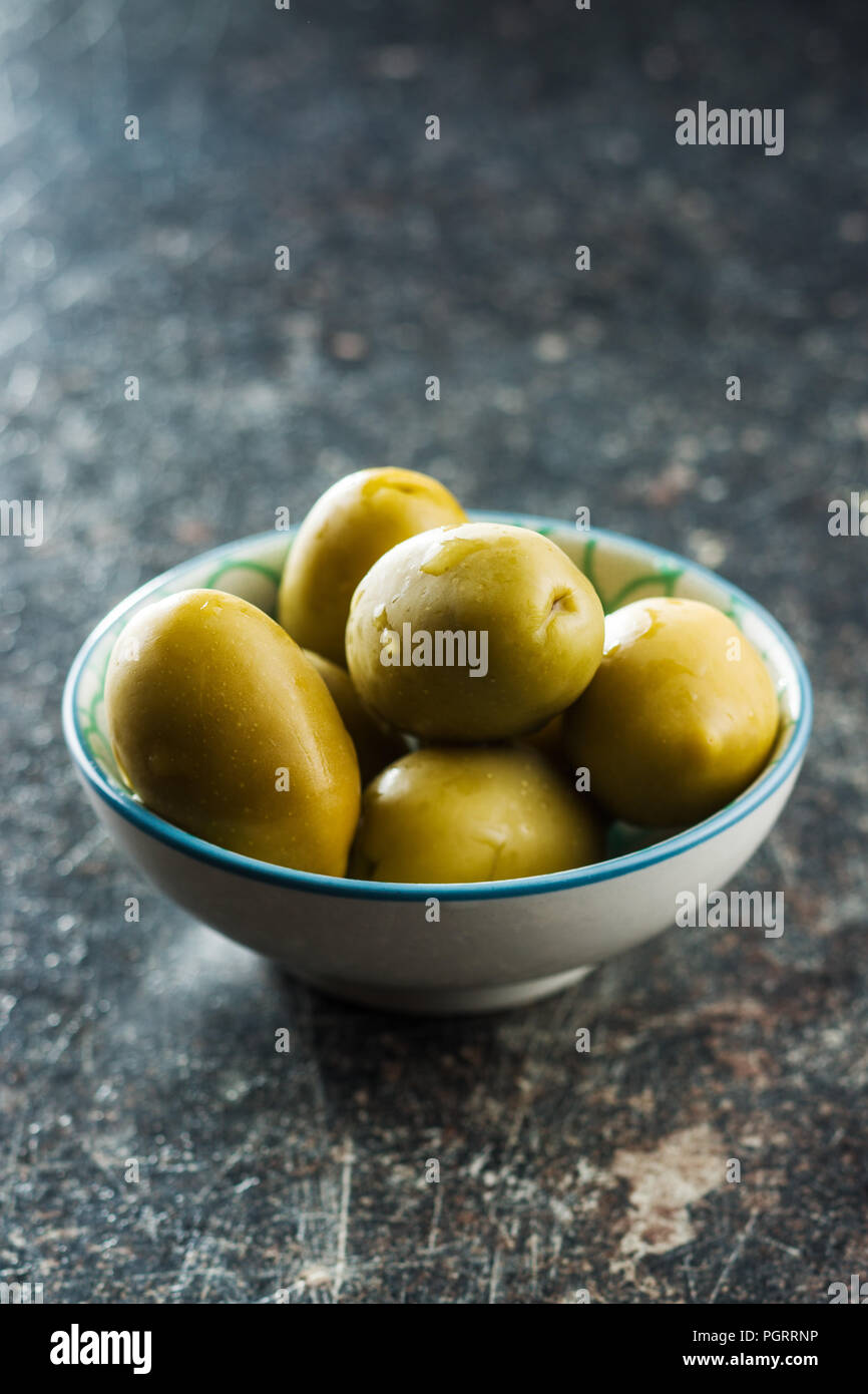 The green olives in bowl. - Stock Image