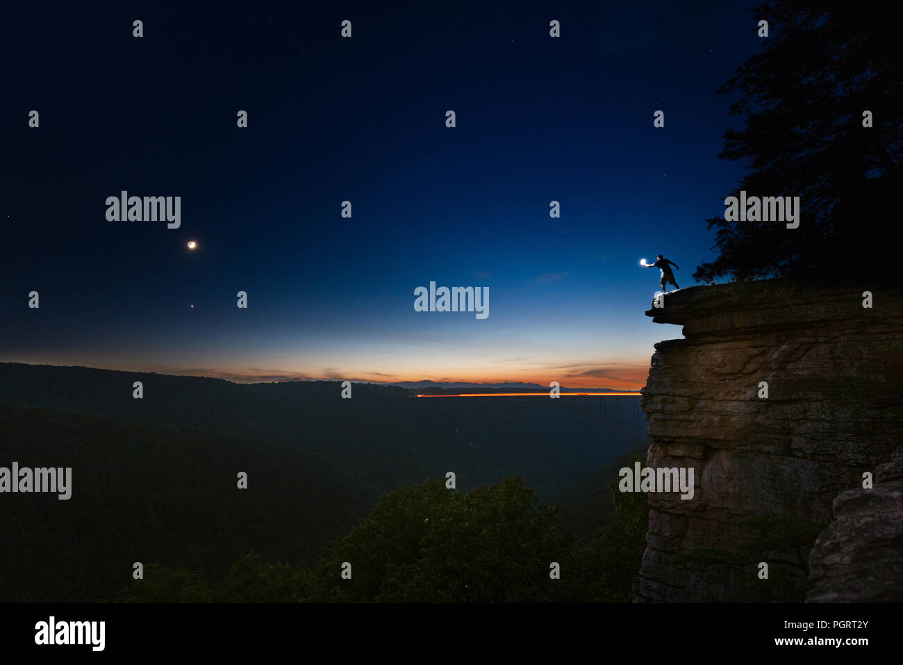 A man stands silhouetted against the sky on the edge of a cliff with a lighted hand reaching across a chasm opposite the crescent moon in the night. - Stock Image