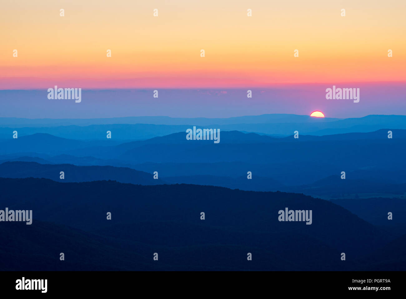A sliver of the sun can be seen dropping below the distant blue mountain ridges of West Virginia, giving the impression of ocean waves. - Stock Image