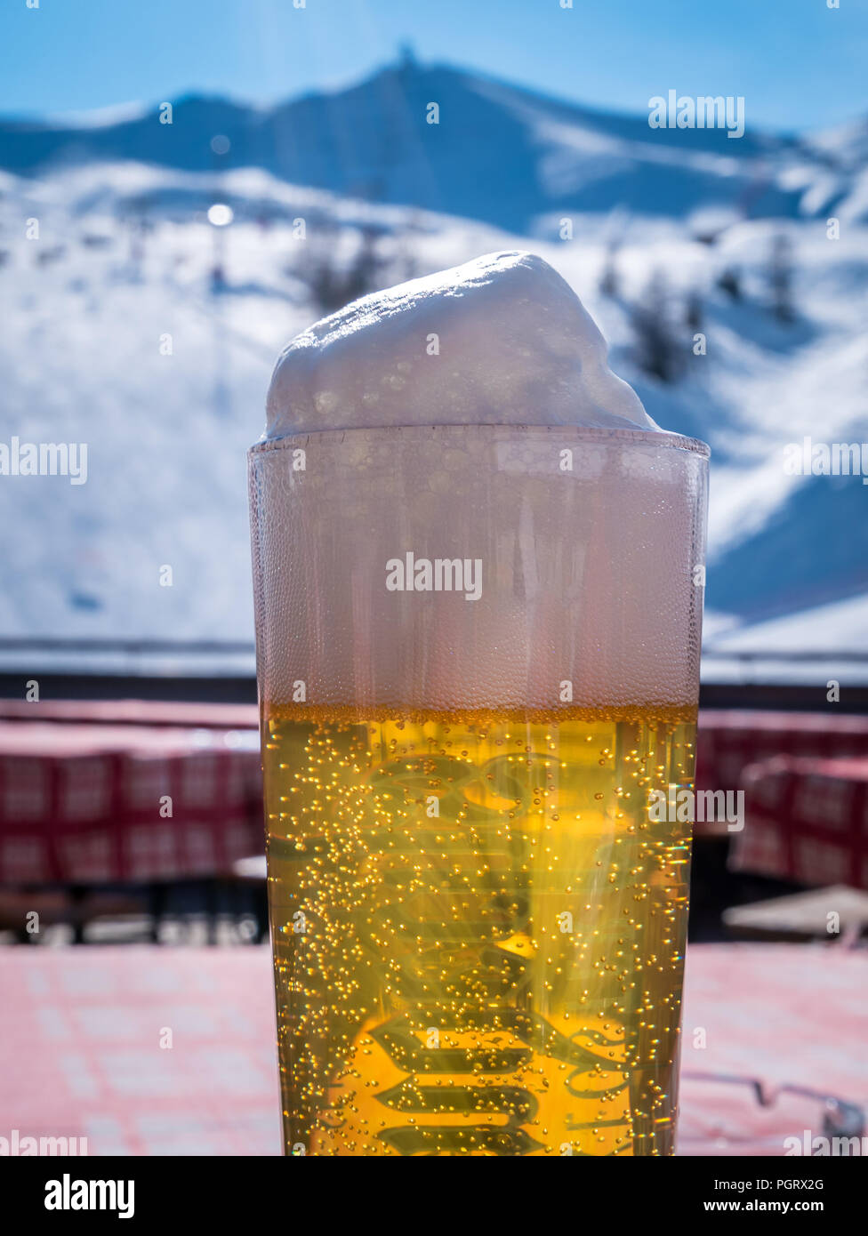 Close-up of beer foam. Draft beer in glass with winter landscape in background. Ski slope in sunny weather. - Stock Image