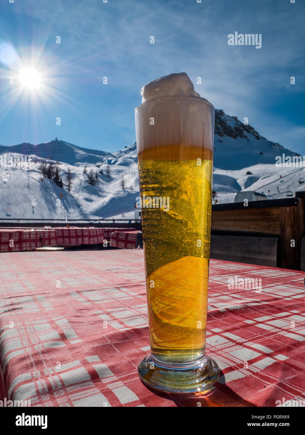 Large draft beer glass on a table in the alps. Ski hill or slope and sun light in background. - Stock Image