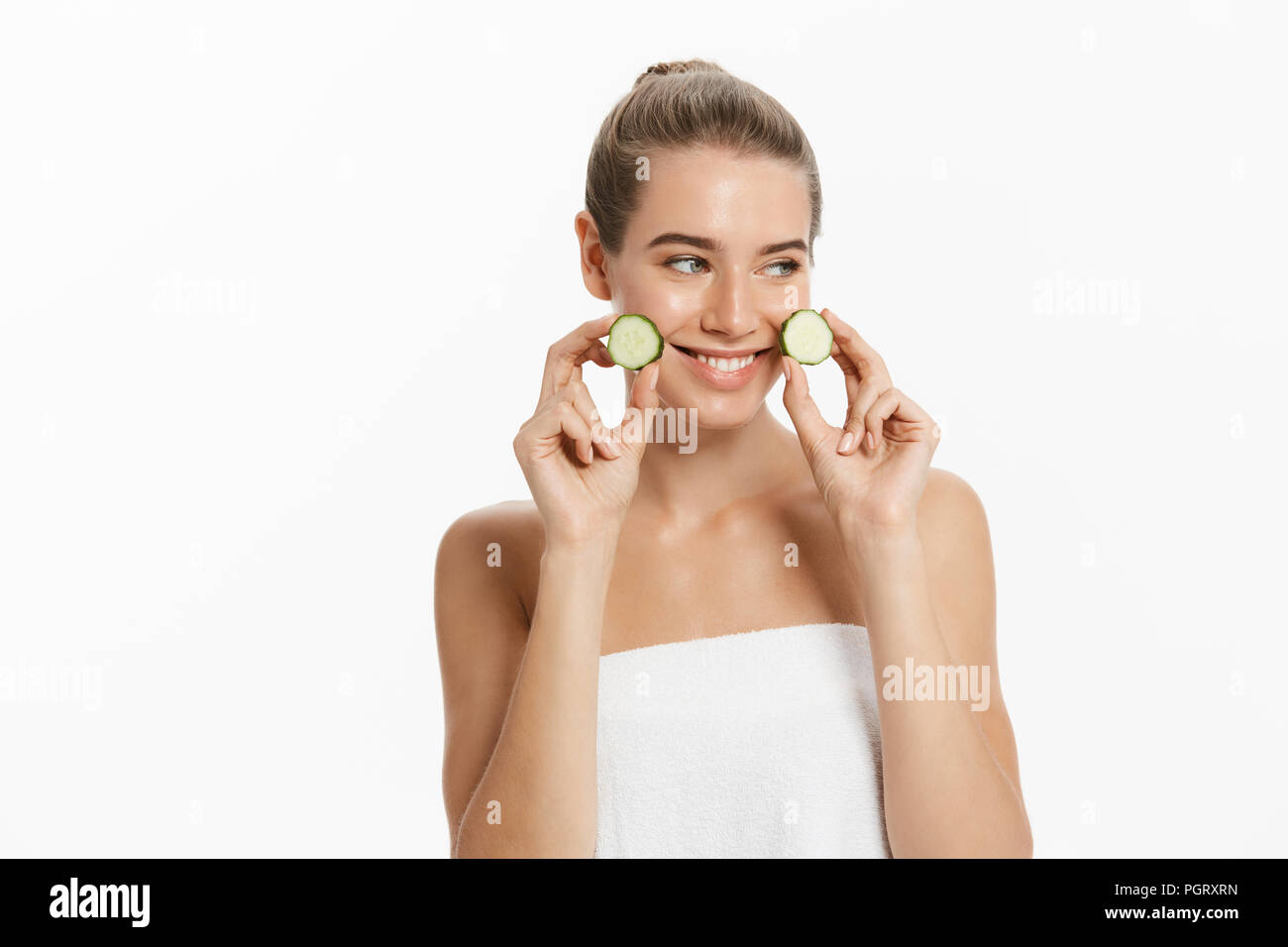 Young woman holding cucumber slices isolated on white background - Stock Image