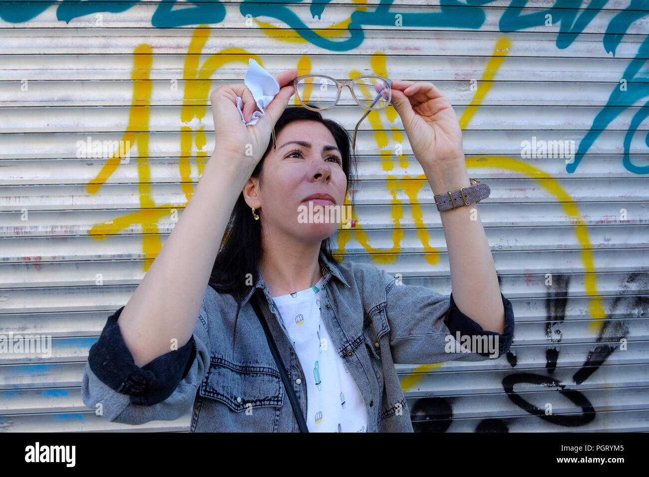 Young adult woman cleaning glasses on the street, - Stock Image