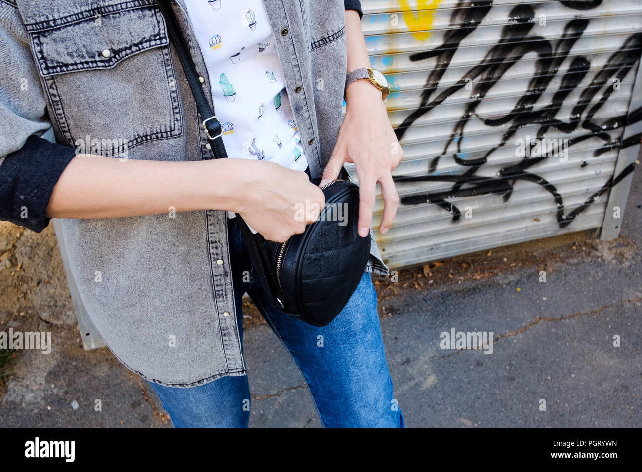 Young adult woman closing her handbag on the street, - Stock Image