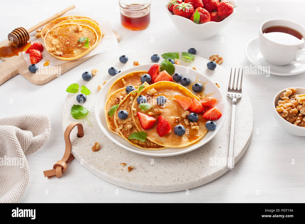 pancakes with blueberry strawberry honey and nuts for breakfast - Stock Image