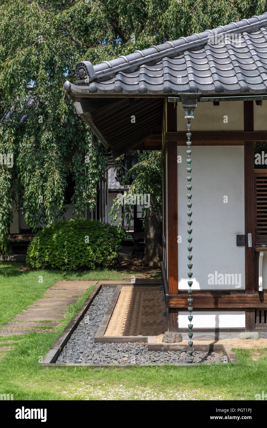 Corner of traditional house with traditional Japanese drainpipe in a Japanese garden. - Stock Image