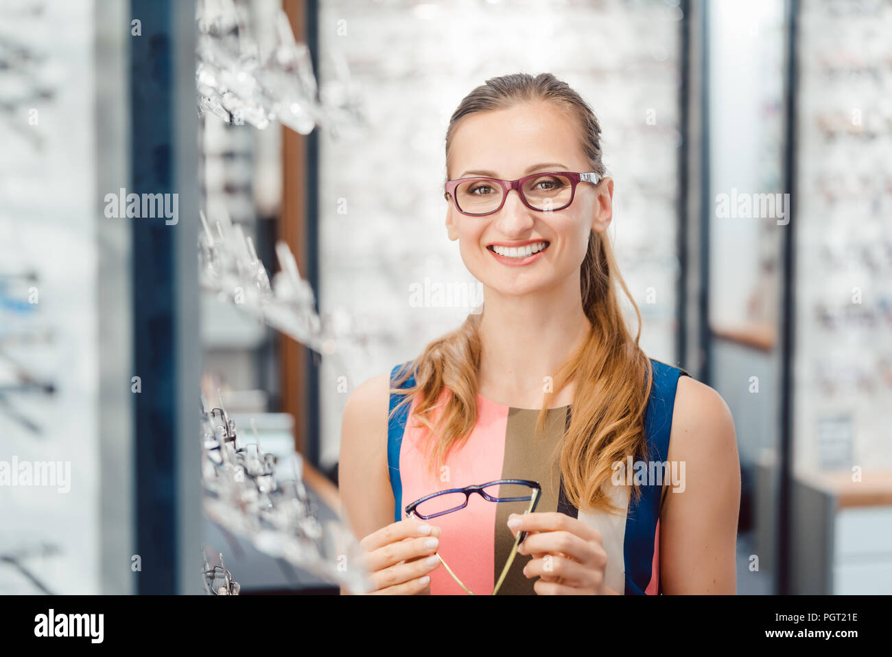 Woman being satisfied with the new eyeglasses she bought in the store - Stock Image