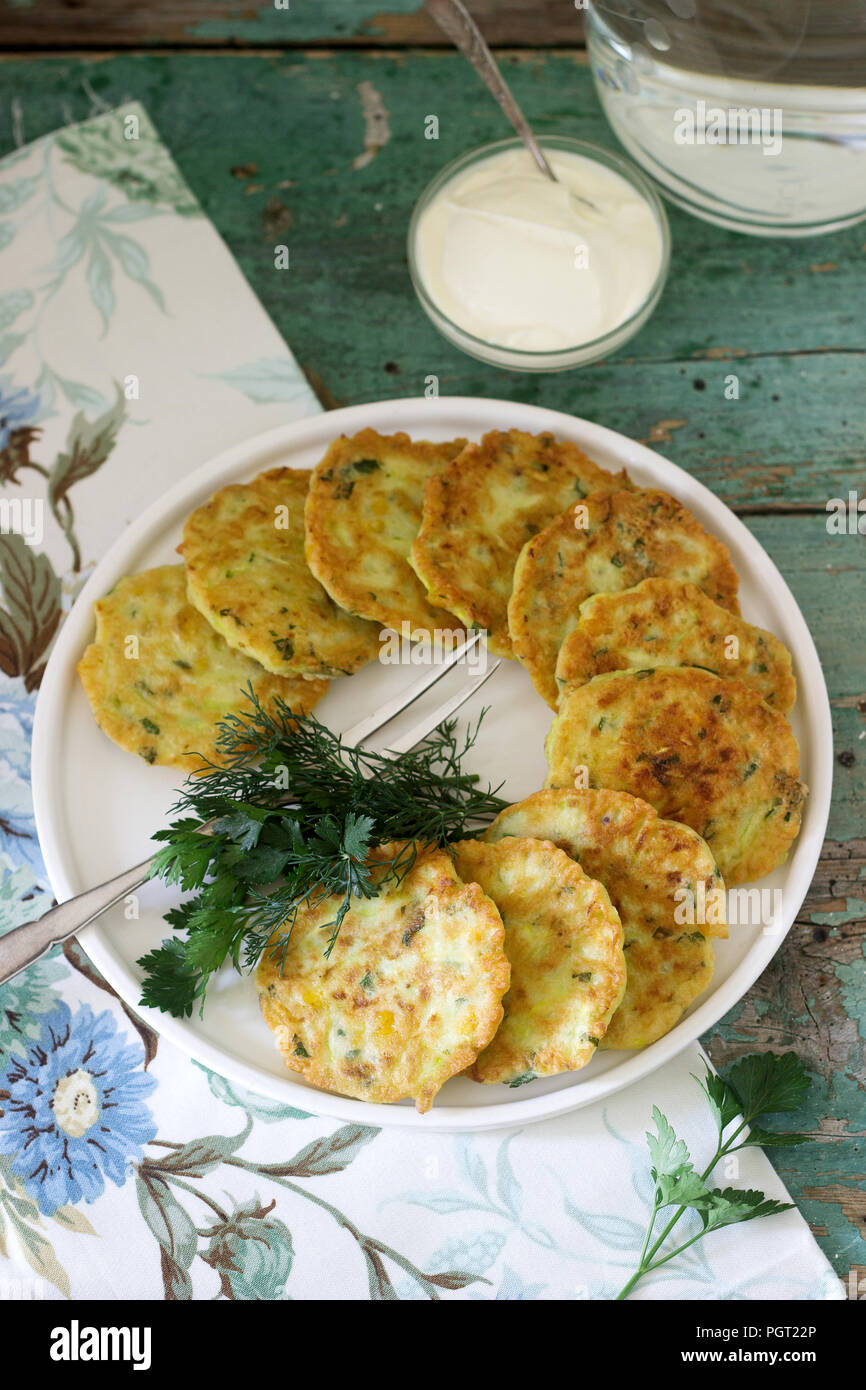 Pancakes with zucchini and sweet corn, served with sour cream, parsley and dill. Vegetarian food, selective focus. Stock Photo