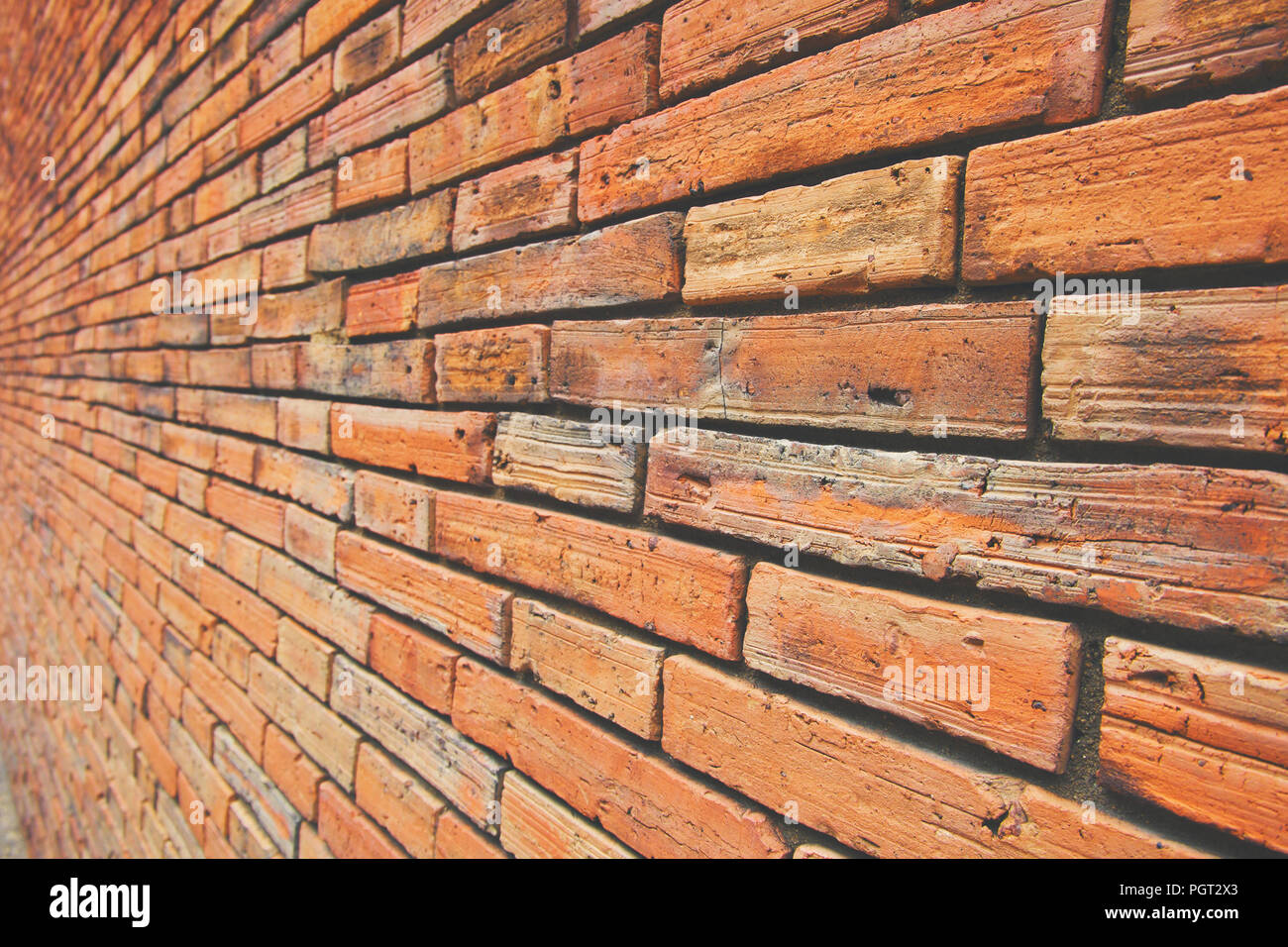 Ancient block wall with brown and orange tone, Side or Oblique view, Old square pattern, Texture background. - Stock Image