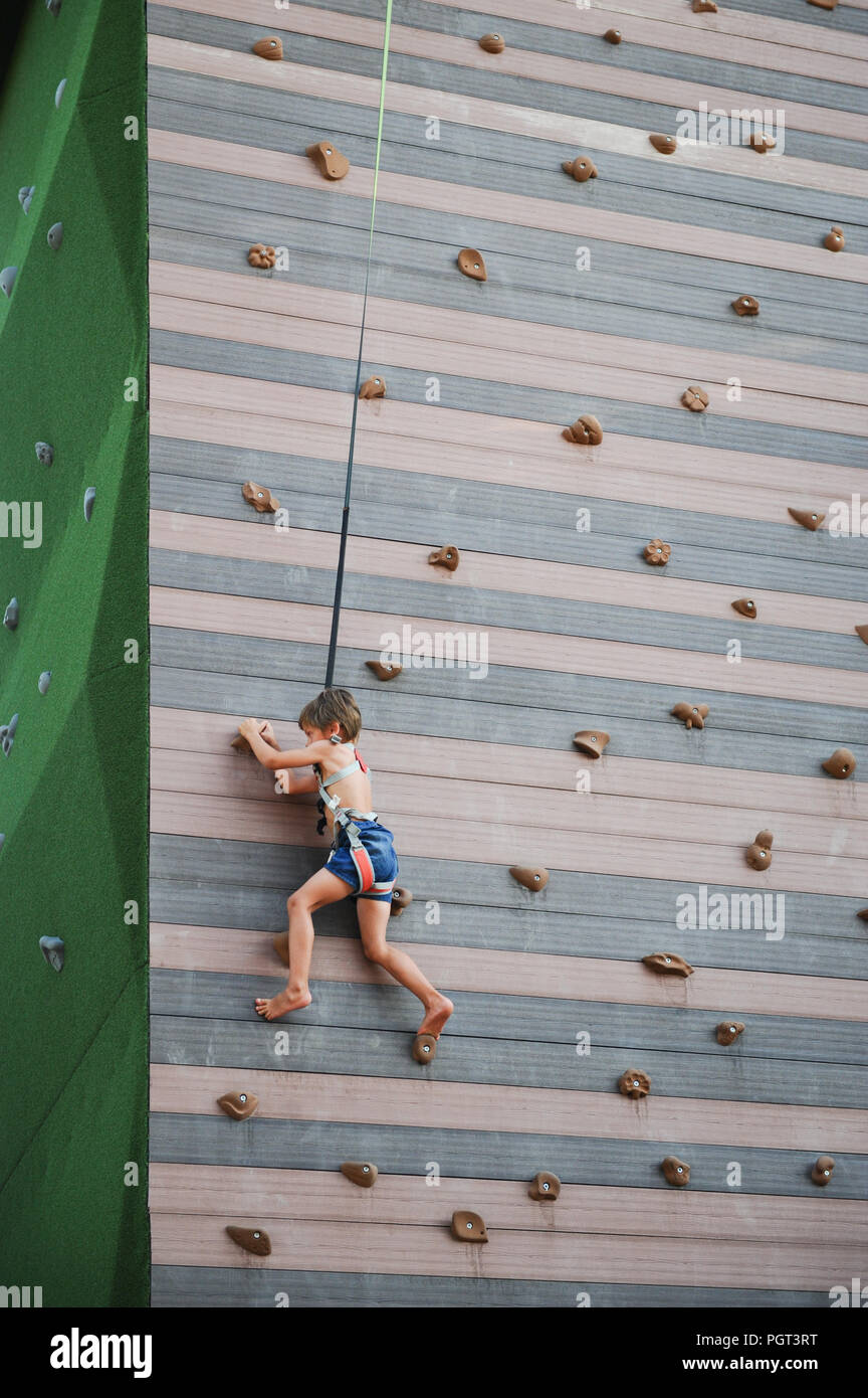 Little boy climbing up brave at playground outdoors sport leisure - Stock Image