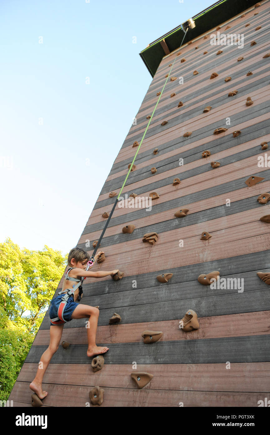 brave little healthy child climbing high rock wall in sport playground outdoors - Stock Image