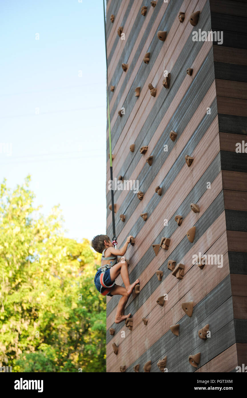 small boy with climbed equipment moving towards top of climbing wall - Stock Image