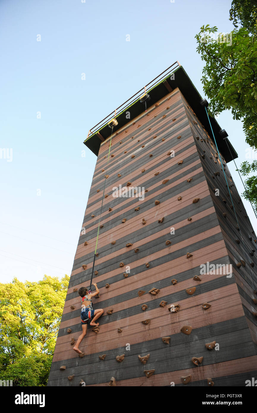 little athletic strong boy climbing on high tower rock wall outdoors sport copyspace - Stock Image