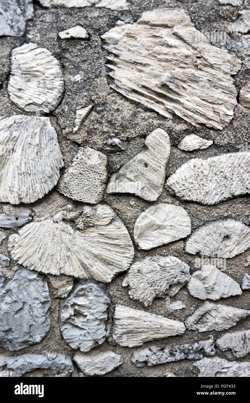 A wall made of stones, possibly designed motifs of 19th-century architecture - Stock Image