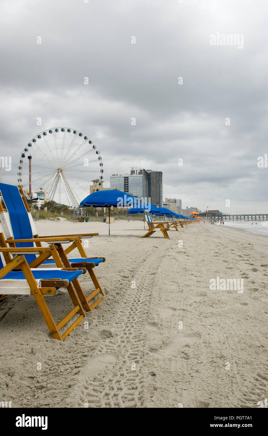 Empty blue chairs and umbrella line the seashore on a dreary day at Myrtle Beach SC USA - Stock Image