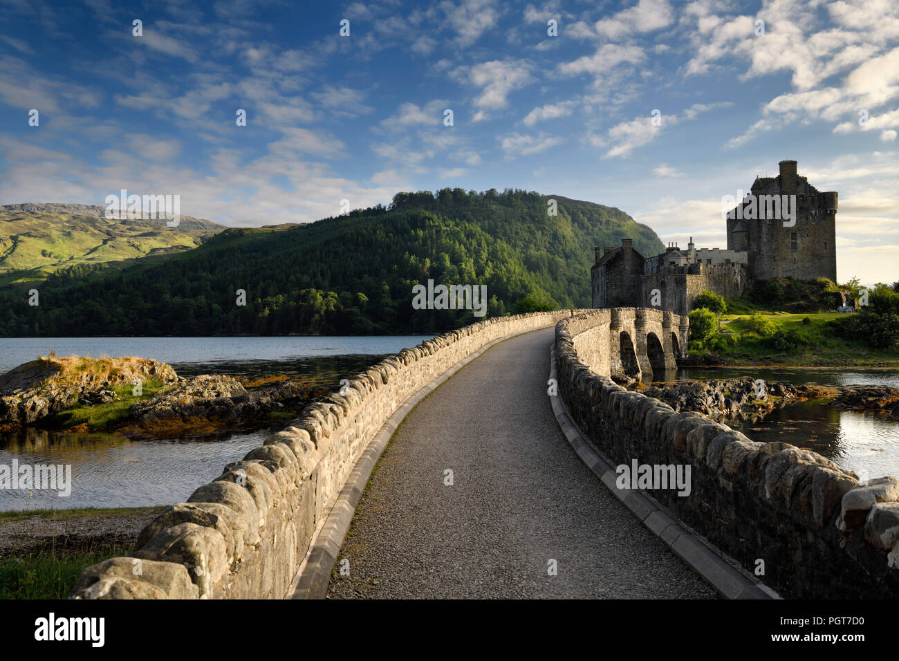 Evening light on new stone arch footbridge to restored Eilean Donan Castle on Island at three lochs in Scottish Highlands Scotland UK - Stock Image