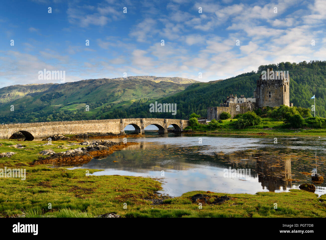Evening light on restored Eilean Donan Castle with sun on added stone arch footbridge to the Island in Scottish Highlands Scotland UK - Stock Image