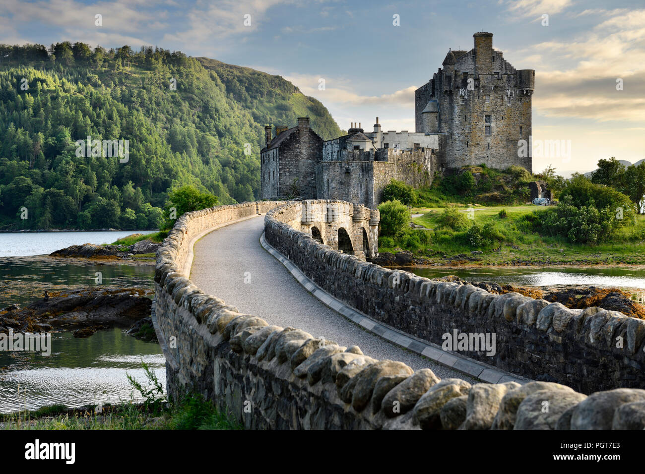 Evening light on restored Eilean Donan Castle on Island at three lochs with added stone arch footbridge Scottish Highlands Scotland UK - Stock Image