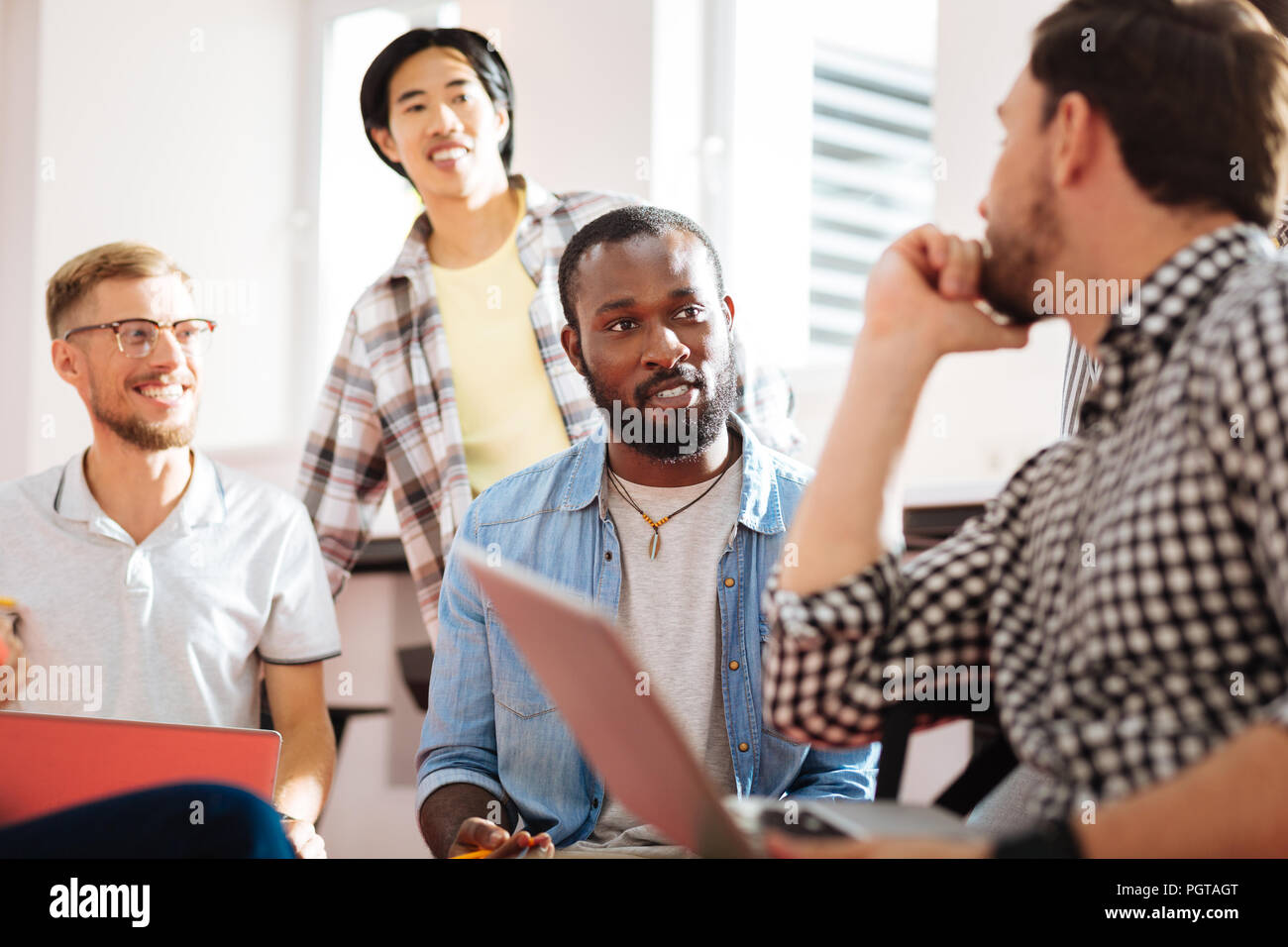 Clever young men enjoying spending time together and looking interested - Stock Image