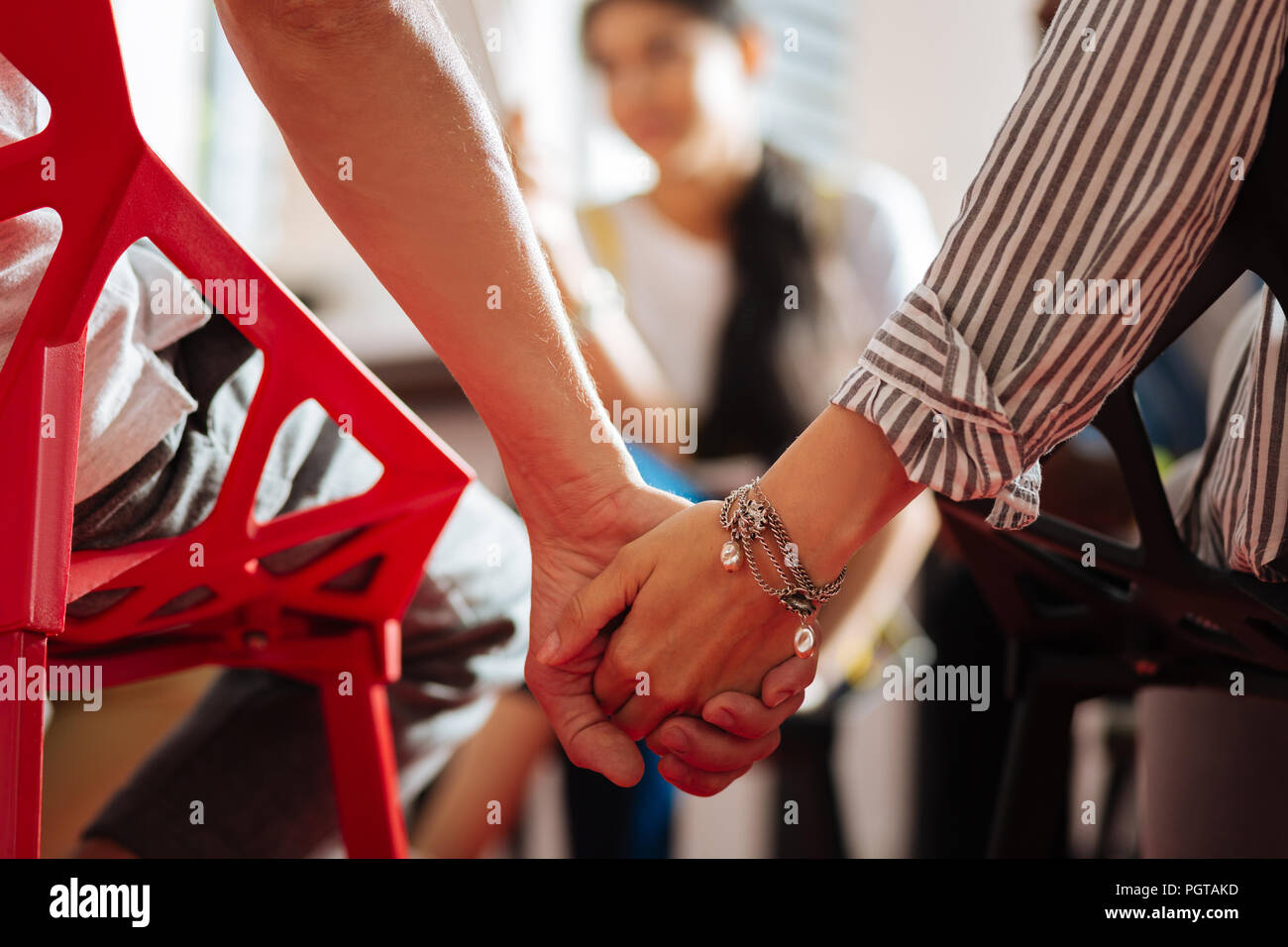 Two people sitting to together and holding hands during the psychological session - Stock Image