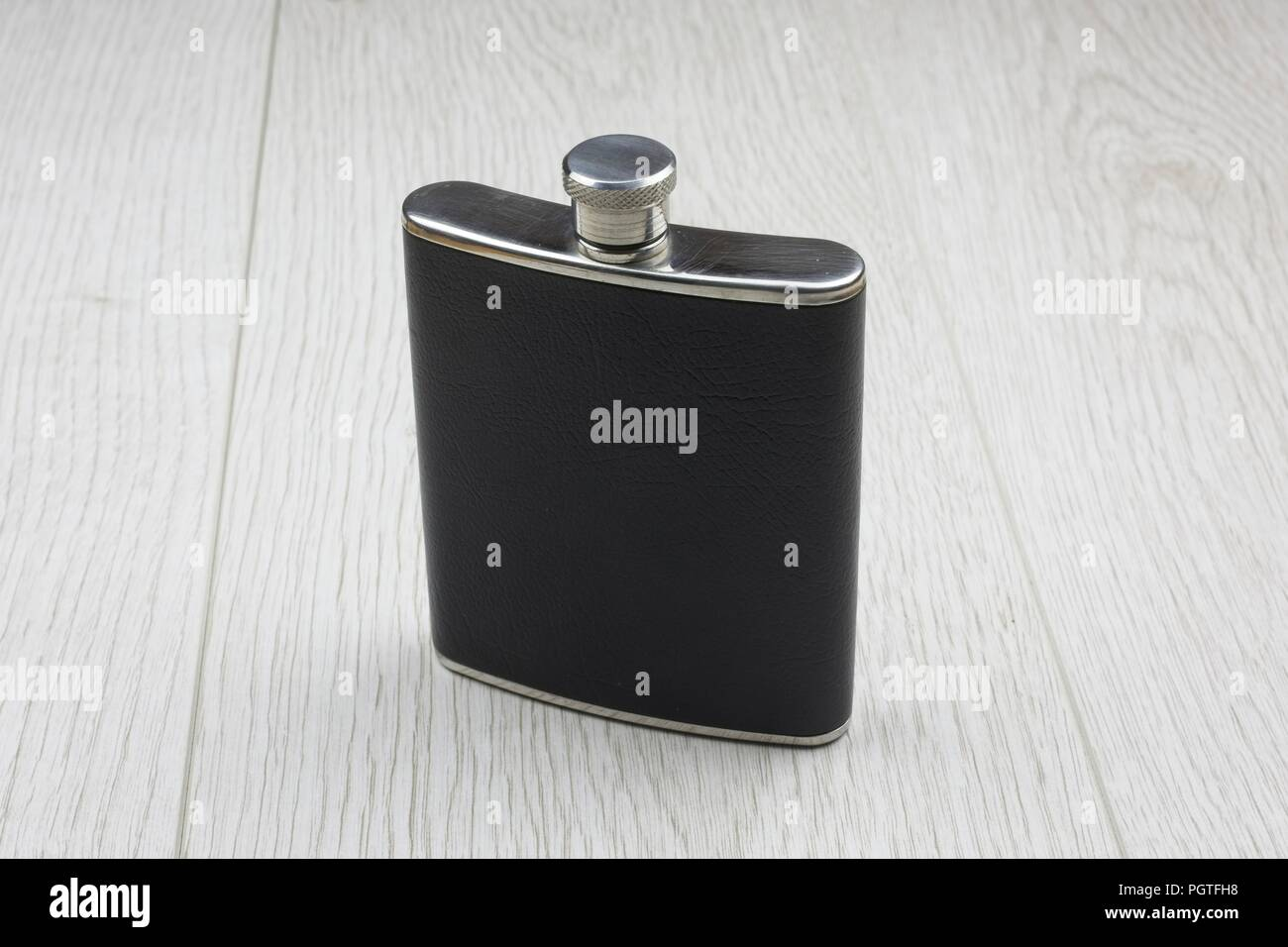 Leather covered hip flask - Stock Image