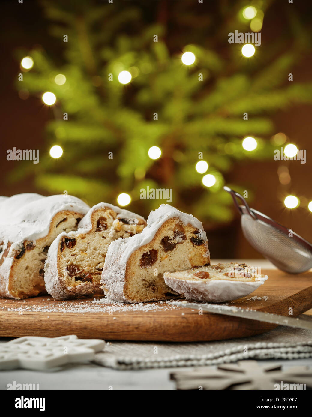 Stollen, traditional German Christmas yeast cake with raisins on the table, fir tree lights bokeh on the background - Stock Image