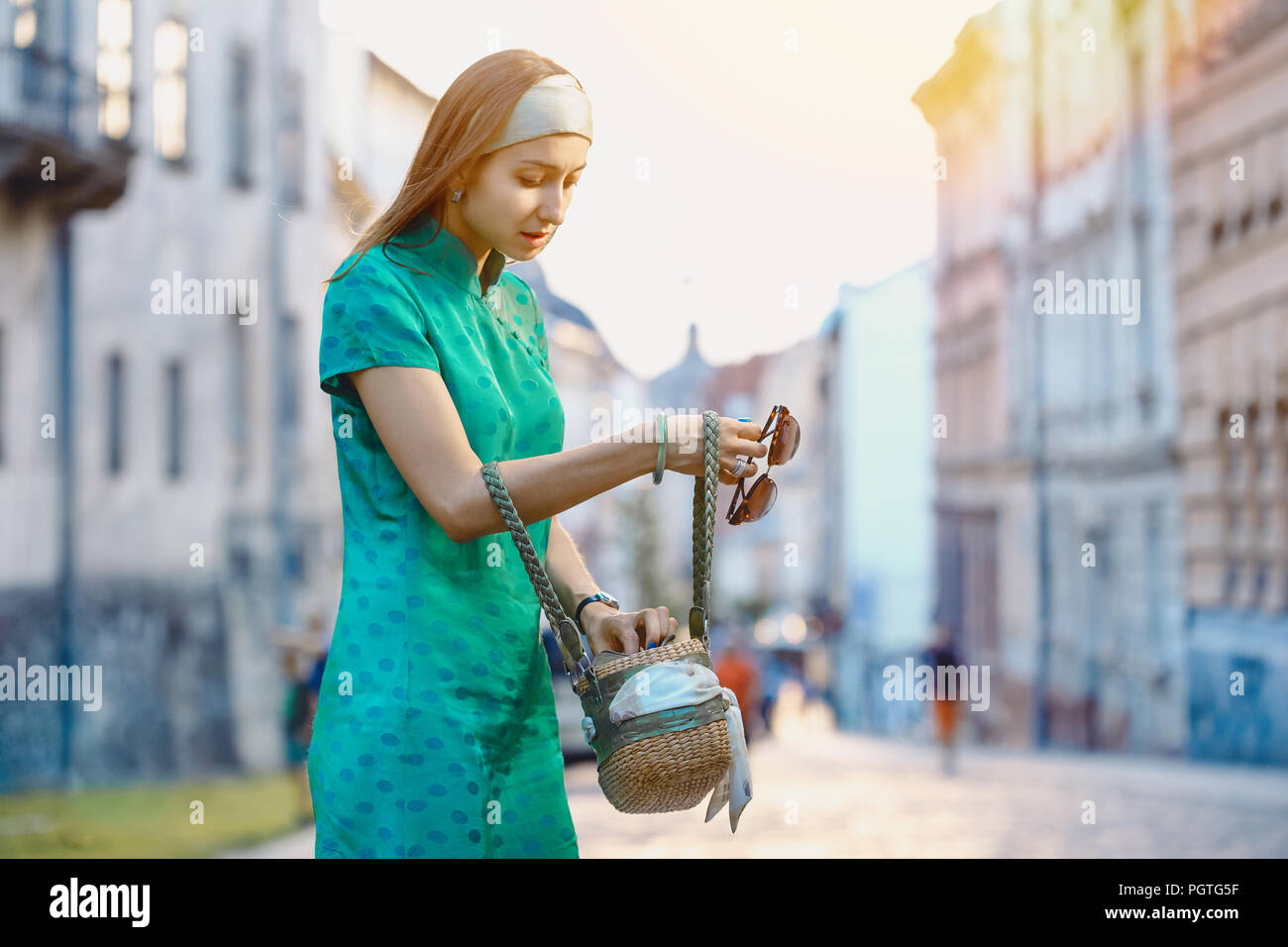 Young beautiful fashionable lady wearing green dress searching for something in her hand bag on a street of the old city. Female fashion. City lifesty - Stock Image