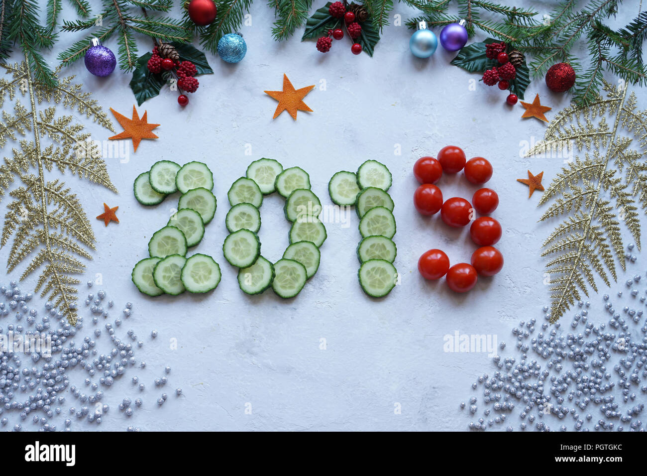 New Year's collage, healthy lifestyle, figures from cucumber and cherry tomatoes - Stock Image